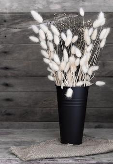 Букет из белых сухих цветов в черной эмалированной вазе