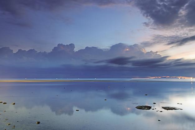 劇的な雨の雲、海、夕暮れの空。長時間露光技術