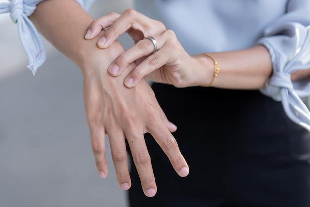 痛みで手首に触れる手