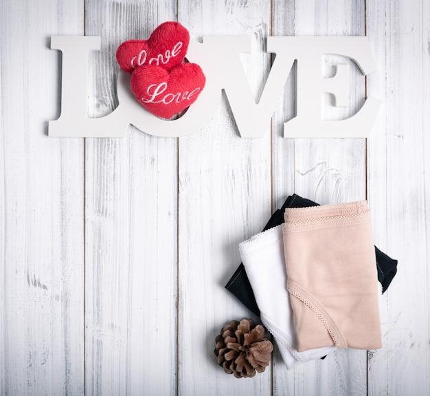 折り畳まれた女性のパンティー、愛ボード、心と松ぼっくり
