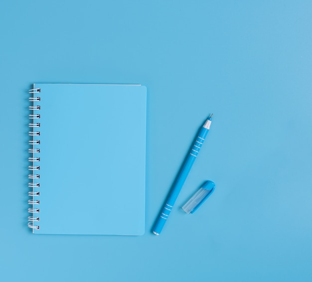 Синий набор блокнот и ручка на синем столе, вид сверху