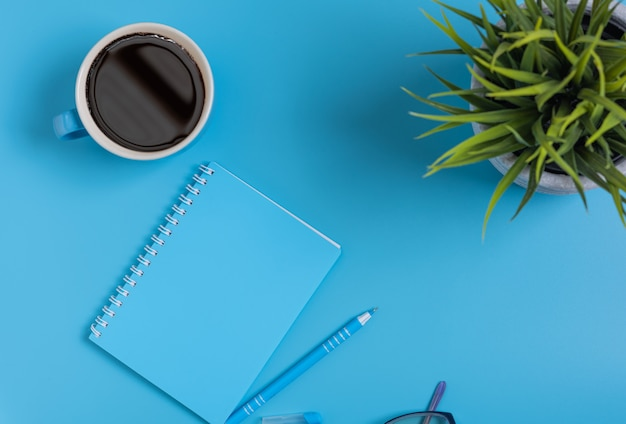 メモ帳、ペン、眼鏡、コーヒーカップ、トップビューの作業スペースブルーセット