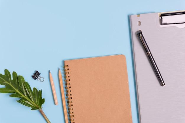 Работает в темпе композиции с файлом документа, блокнотом, ручкой, карандашом и зелеными листьями, вид сверху