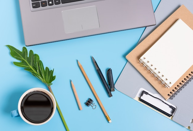 Композиция работает с кофейной чашкой, файлом документов, ноутбуком, ноутбуком и зелеными листьями, вид сверху