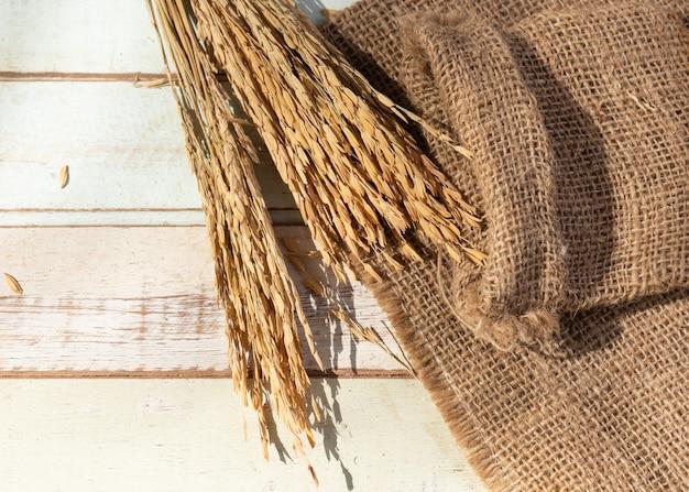ライスタイジャスミンと黄麻布または荒布木製テーブルの上の花束乾燥耳、トップビュー