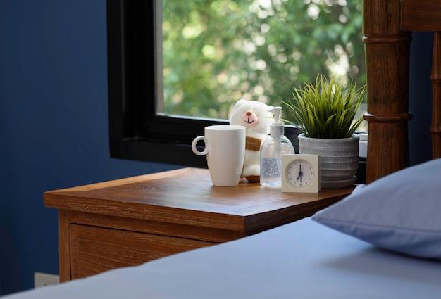 Дезинфицирующее средство для рук, белая чашка, плюшевый мишка и будильник на деревянном столе в синей спальне
