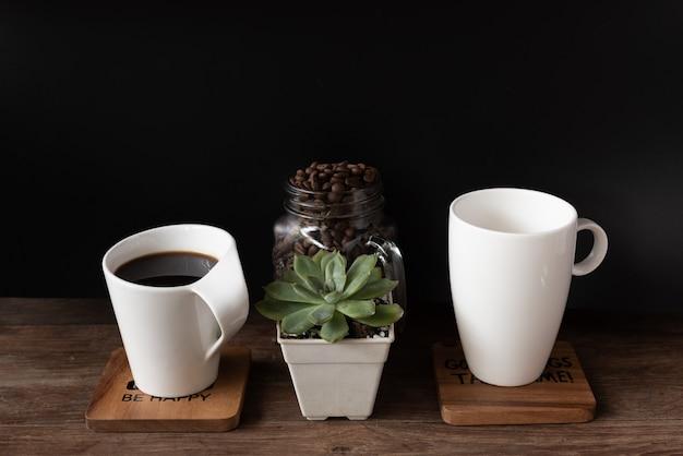 ローストコーヒー豆とフラワーポットの装飾が施された木製のテーブルに白いコーヒーカップ