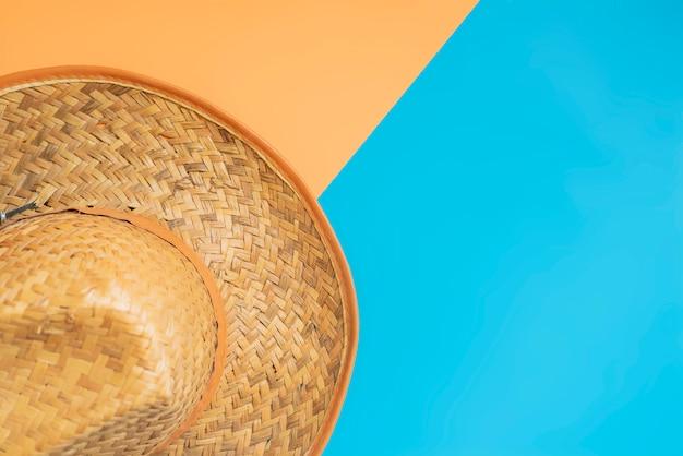 コピースペースを持つ創造的な色の表面上の夏帽子のトップビュー