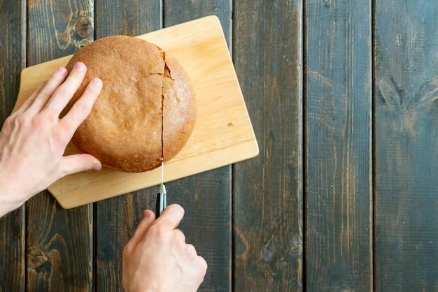 木製の表面にパンを切る手の切断のトップビュー