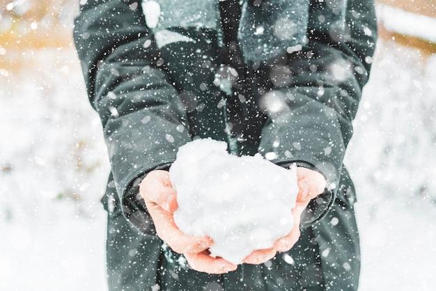 冬の日の屋外で雪を保持している手を閉じる
