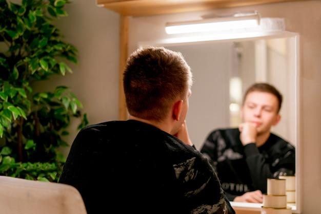 Человек делает сделать перед зеркалом в спальне у себя дома