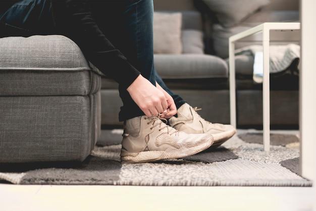 Крупным планом человек надевает повседневные кроссовки и завязывает шнурки на диване и ковре