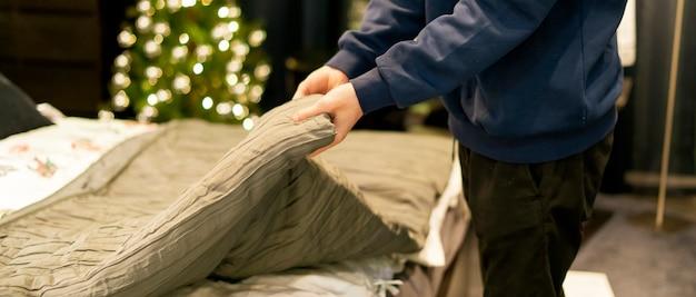 自宅の寝室でベッドを作る若い男を閉じる