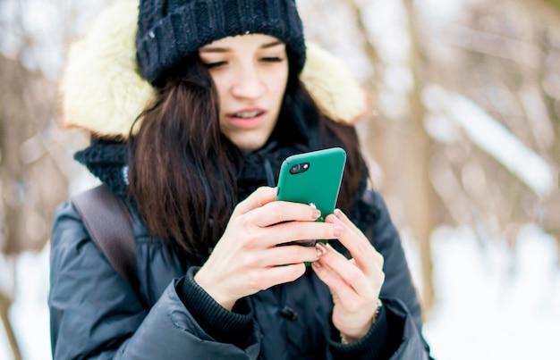 冬の日に屋外のスマートフォンを使用して女性のティーンエイジャーの肖像画