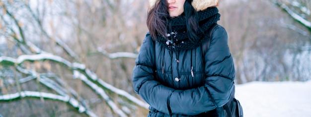 冬の自然の雪に覆われた公園屋外で歩くティーンエイジャーの女の子