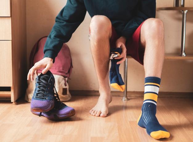 Крупный план спортсмена в раздевалке надень носки и надень спортивную одежду