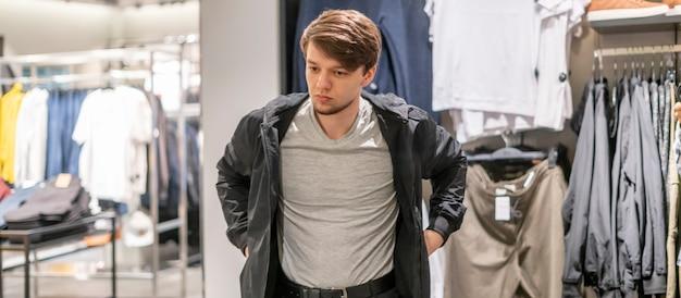 青年実業家が店で新しいジャケットを試着します