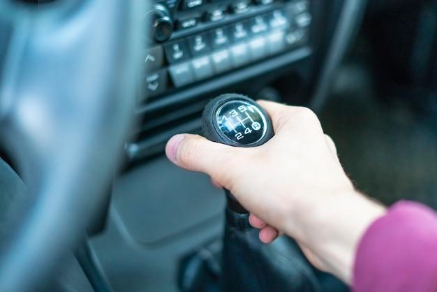 車のマニュアル伝達スティックを持っているドライバーの手を閉じる