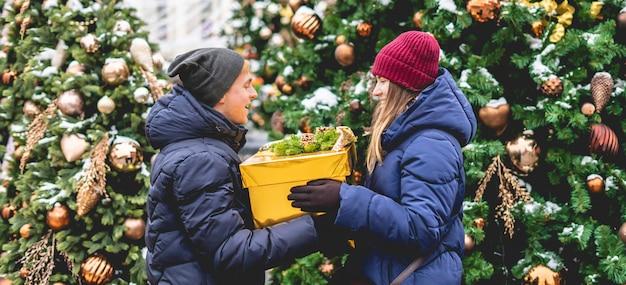 Молодой человек, давая рождественские мерзавец своей подруге возле сосны на открытом воздухе