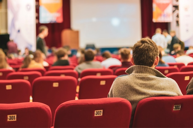 ビジネス会議の講堂の人々。後ろに座って見ている人