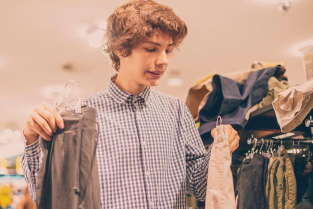 店で正しい服を選んで選ぶ若いティーンエイジャーの肖像画