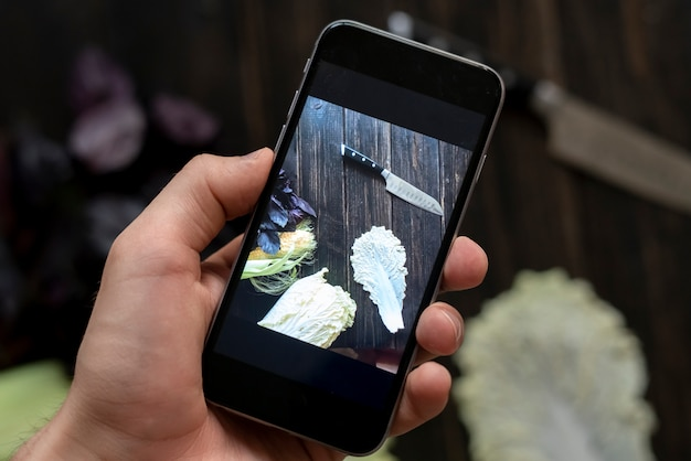 Закройте руки над темной таблицей, делая фотографию продукта питания с телефоном