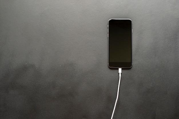 分離されたスマートフォンに挿入された充電ワイヤ