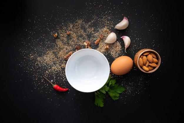 黒いテーブルの上の空の白いセラミックプレート、調理のための新鮮な食材、コショウ、食器