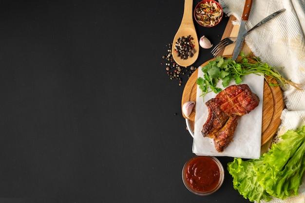 リブアイステーキのグリル、ハーブの葉とスパイス、コピースペース付きのトップビュー