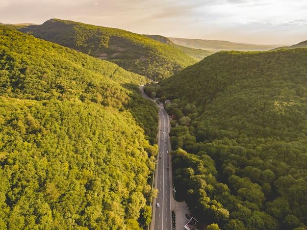 緑の森で覆われた山々の間の広い高速道路の空撮
