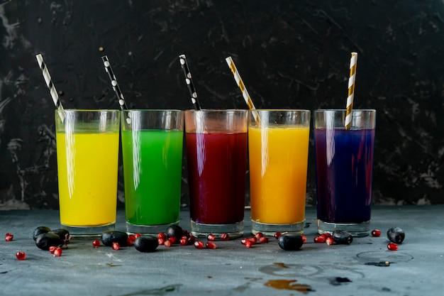 暗い面に赤、黄、緑、オレンジ、紫の新鮮なスムージーのグラス