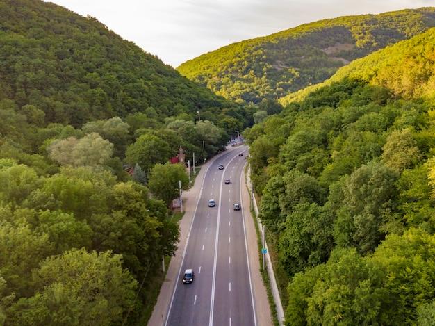 Аэрофотоснимок широкого шоссе между горами, покрытыми зелеными лесами