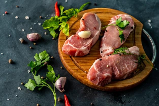木製のスライスやまな板の上のスパイシーな生肉、未調理の肉に塩を入れる
