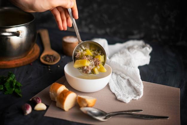シェフの手は白い空のボウルに新鮮な熱いスープを注ぐ、食品の調製