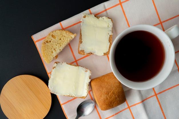 Человек кладет кусок масла на ломтик хлеба и чашку кофе на стол, готовит завтрак