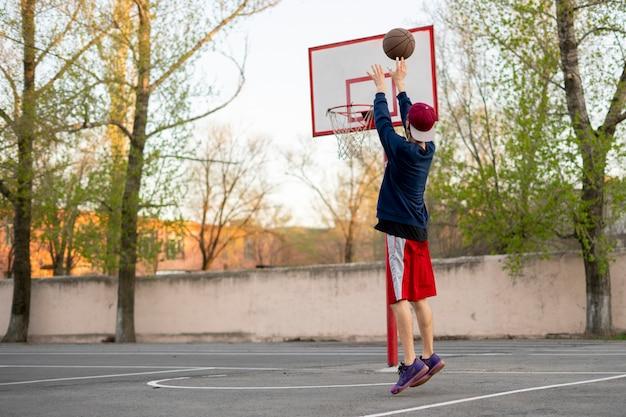 市のストリートコートで屋外で練習射撃訓練をしているバスケットボール選手