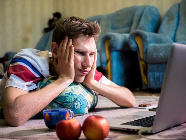 Портрет молодого скучающего человека, лежащего перед ноутбуком