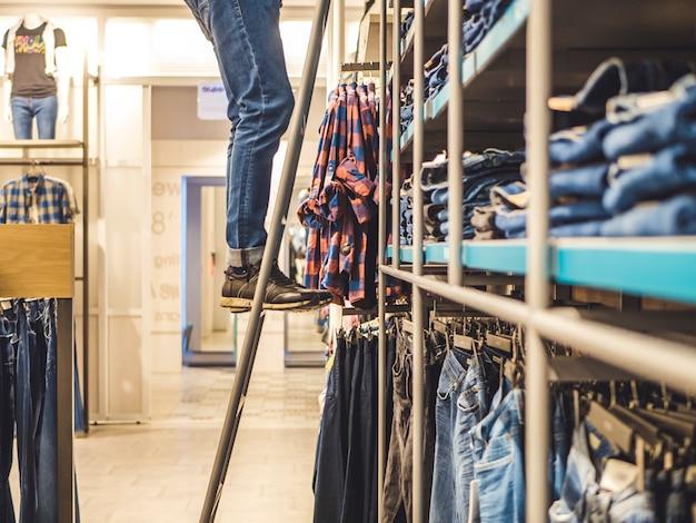 男は梯子の上の洋服店でジーンズを選ぶ