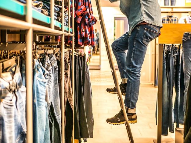 Мужчина на лестнице подбирает джинсы с полки в магазине одежды