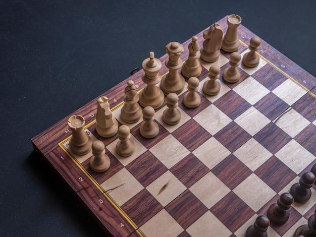 黒いテーブルの上のデフォルトの位置のチェスボードゲームを閉じる