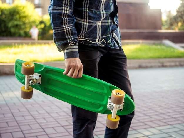 現代の新しいスケートボードペニーボードと街を歩いて若い男の体の一部を閉じる
