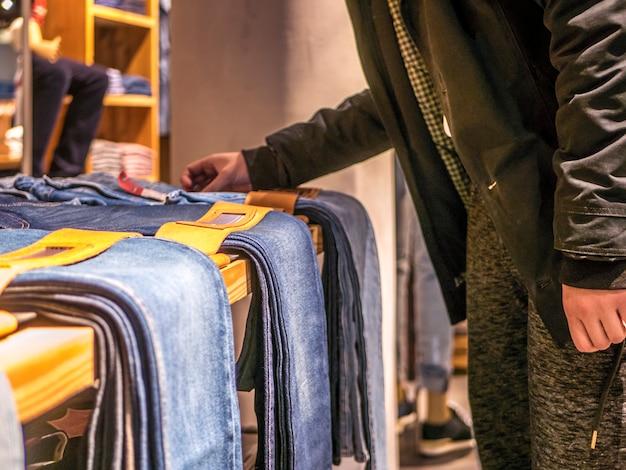 Закройте вверх руки человека, выбирая и покупая джинсы в магазине