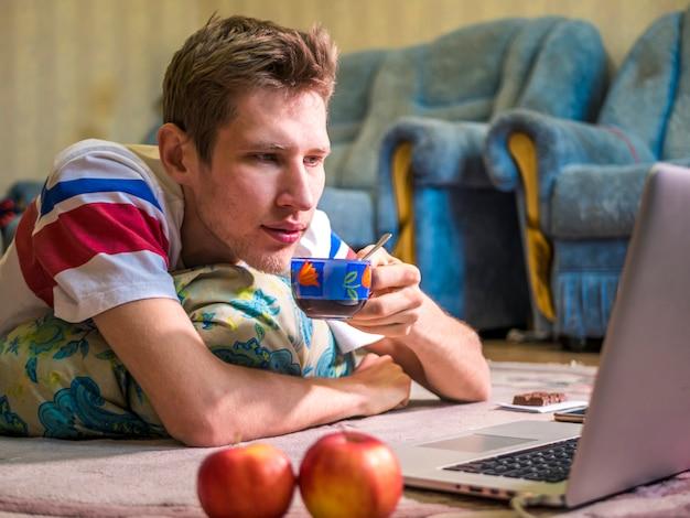 若い男性が自宅でノートパソコンの前でコーヒーを飲む