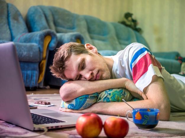 床のカーペットの上に横たわっている間ノートパソコンの前で寝ている若い男