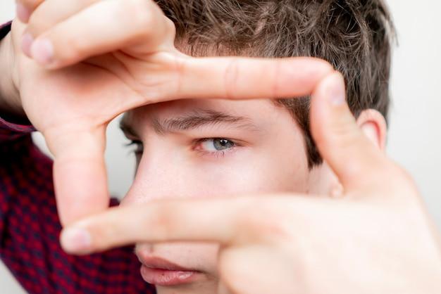 Молодой человек делает рамку на лице на светлом фоне