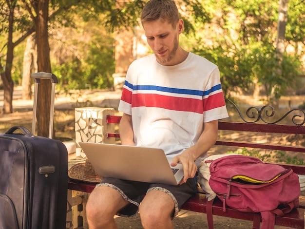Бородатый туристический мужской портрет работает на ноутбуке с большими чемоданами