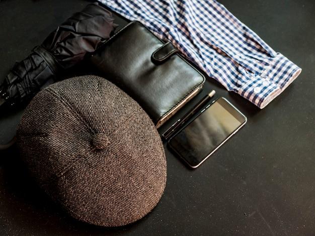 Плоские лежали мужские традиционные вещи на темной поверхности ноутбука зонтик телефона и шляпа