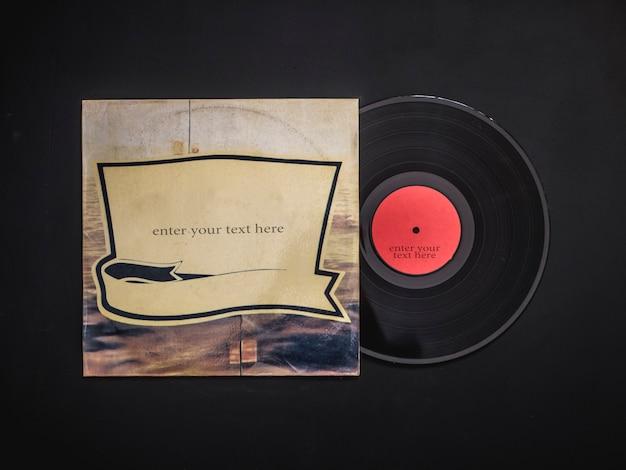 黒いテーブルの上のカバーから空白のビニールレコードのオーバーヘッドフラットレイアウト