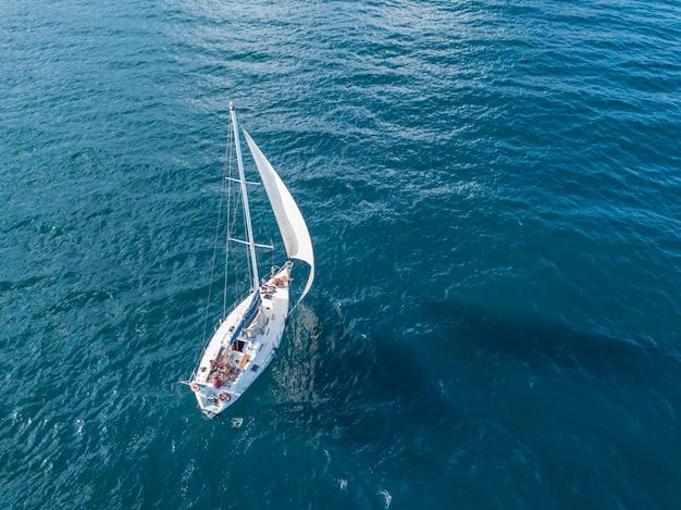 Одинокая изолированная яхта под парусом с высокой мачтой, идущей в неподвижном море с высоты птичьего полета