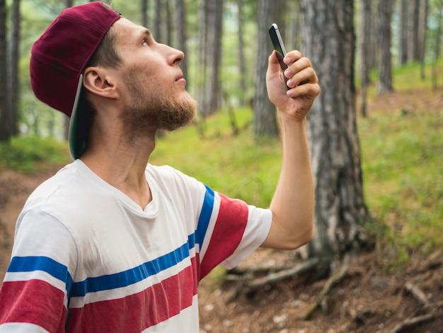 若いひげを生やした流行に敏感なブロガーは森を歩くソーシャルネットワークでライブストリームを作る